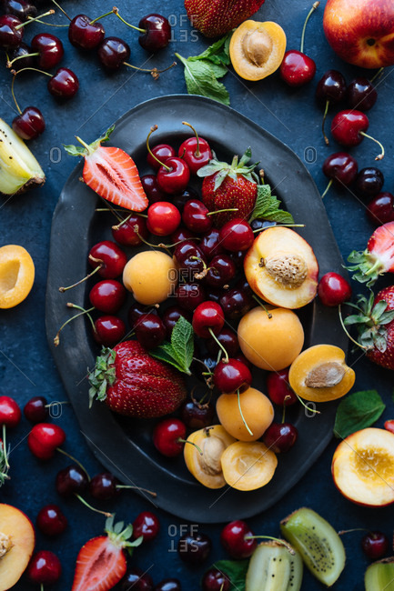Overhead view of fresh summer fruits and berries on dark platter and spilling onto dark table top