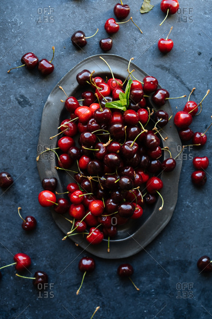 Top down view of heap of dark ripe cherries on dark platter