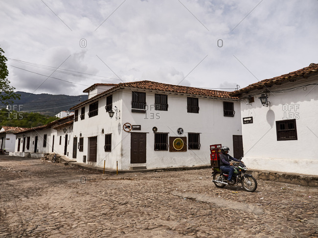 Giron, Colombia - December 29, 2016: Person riding motorcycle on cobblestone streets through town