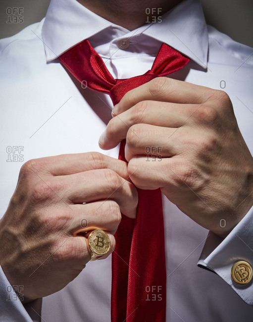 Close-up of a person tying a red tie and wearing a dress shirt with a bitcoin cufflink and a bitcoin ring