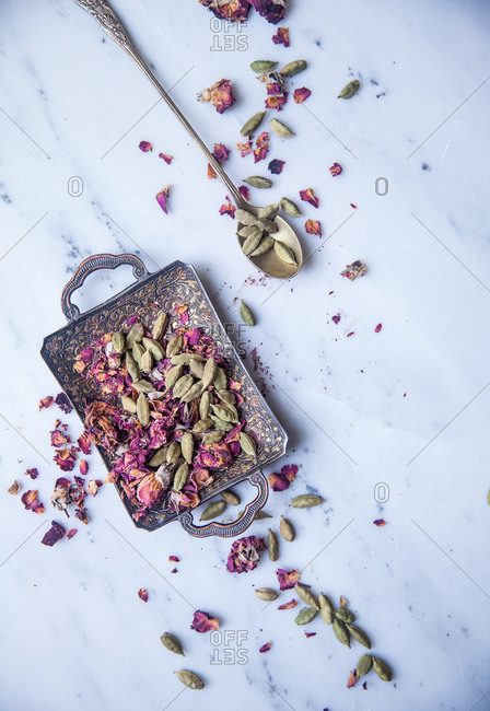 Cardamom and rose petals on a decorative serving tray with spoon