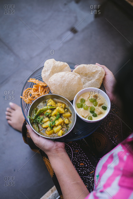 Person holding a plate with Indian food