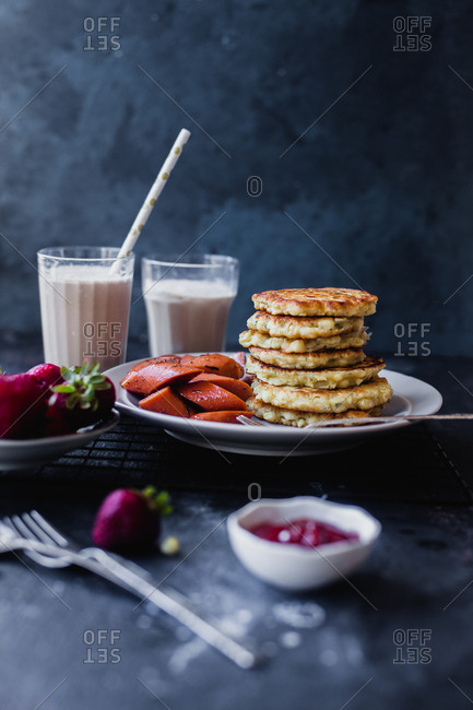 Stack of potato pancakes served with fruit and milk