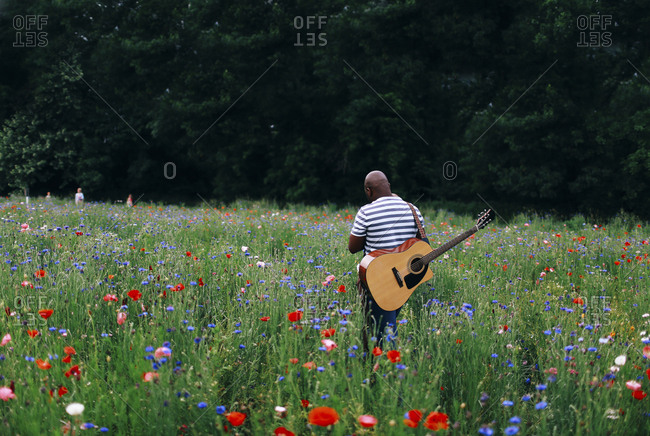 Man with a guitar standing in a field of wildflowers