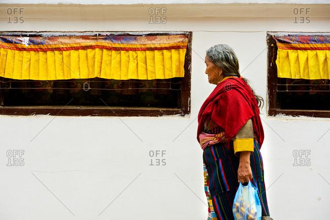 Kathmandu, Nepal - August 3, 2017: Tibetan Woman walking around the Boudhanath Stupa