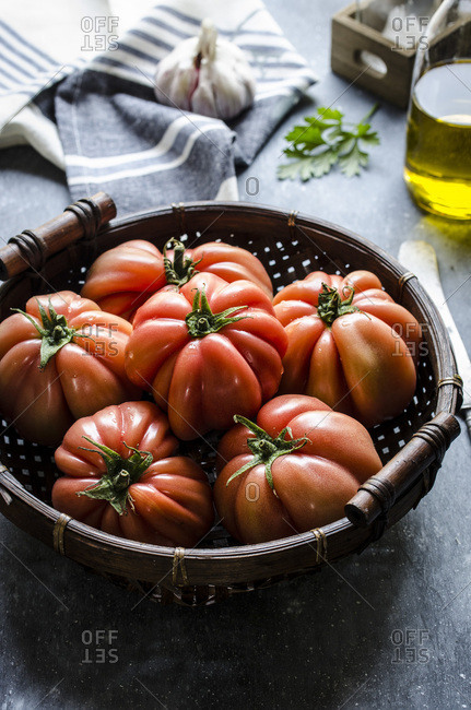 Freshly picked beef tomatoes in a wicker basket against a dark background.