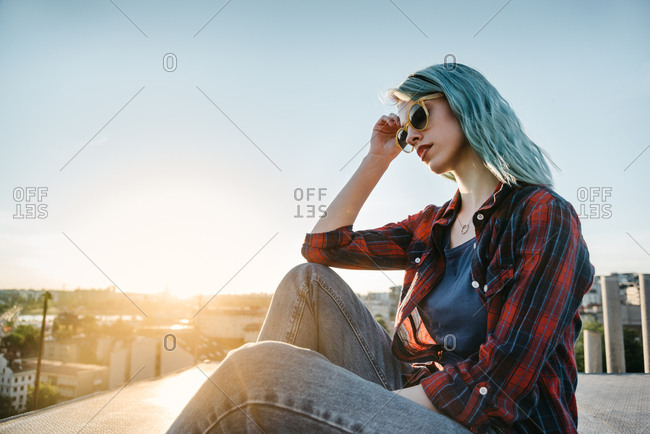Young urban woman in red shirt and blue hair sitting on the top of the roof