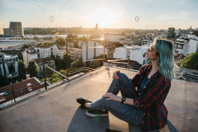 Young urban woman sitting on the top of the roof among beautiful panoramic view of the city