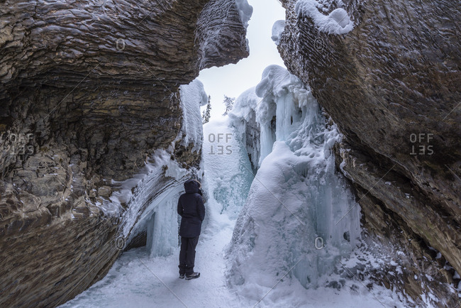 Young woman standing in front of ice and rock formations at Natural Bridge, Yoho National Park, UNESCO World Heritage Site, British Columbia, The Rockies, Canada, North America