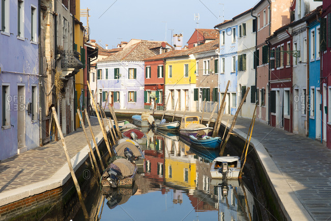 February 12, 2018: Colorful houses and boats next to canal, Burano, Venice, Veneto, Italy, Europe