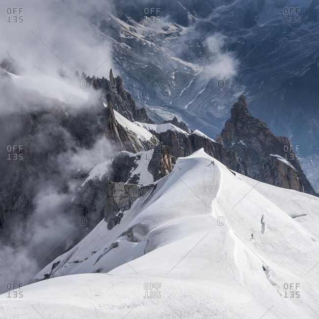 Looking down the ridge into the Vallee Blanche where a small group of climbers are heading into the Vallee below, Chamonix, Haute Savoie, Rhone Alpes, France, Europe