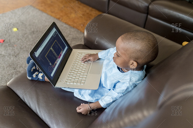 Male toddler sitting on couch using laptop computer