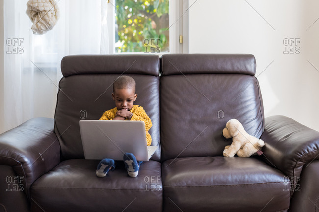 Male toddler sitting on couch using laptop computer at home