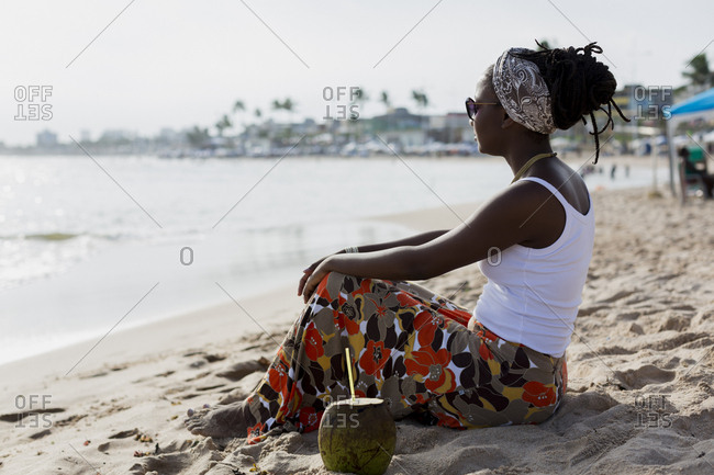 Woman drinking coconut on a brazilian beach. Salvador de Bahia.