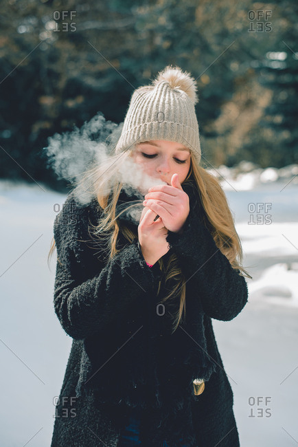 Pretty woman standing and smoking up cigarette in winter nature.