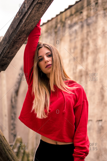 Casual young blonde in red hoodie standing with hand up on grungy background looking sensually at camera.