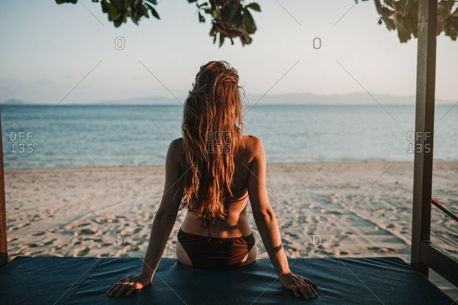 Back view of woman sitting on small wooden hut and looking away at the ocean on beach in Thailand.