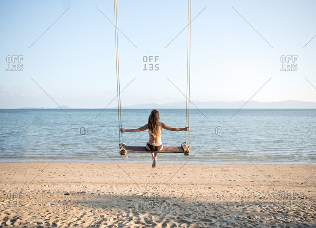 Attractive woman sitting on swings on sandy shore in Thailand.