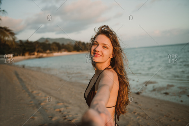 Cheerful young woman standing on beach and holding hand of photographer in Thailand.