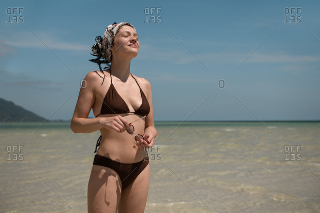 Back view of attractive woman walking on sandy coast at seaside in Thailand.