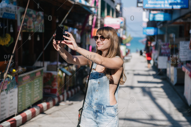 Cheerful young woman taking selfie with camera while standing on street in Thailand.