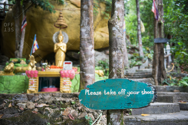 Please take off your shoes wooden sign at golden Buddha statue in Thailand.