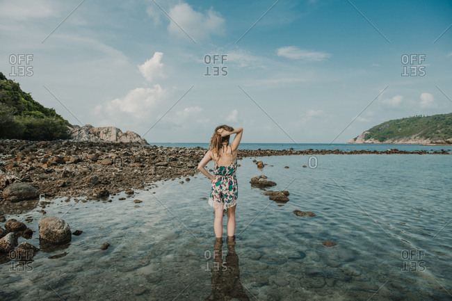 Back view of woman standing on rocky shore at the sea in Thailand.