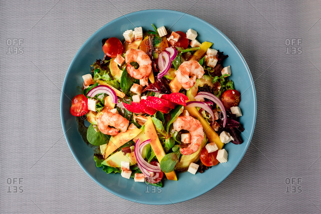 Top view of appetizing vegetables salad served with shrimps on a table.