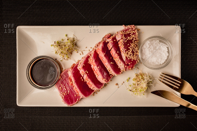 From above tuna steak served with soy sauce on the plate.