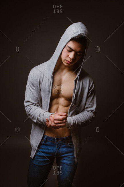 Handsome young man standing in jacket on naked body looking down on dark background