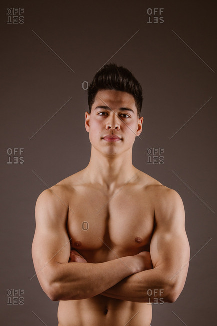 Muscular man posing on dark background