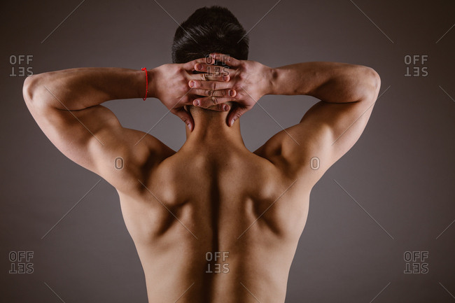 Back view of unrecognizable topless athlete stretching arms raising above head on dark background