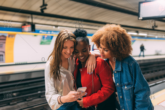 Group of three beautiful young multiracial women traveling on the underground