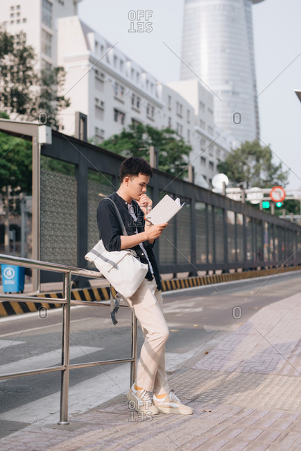 Young asian man was reading book while waiting for a public bus