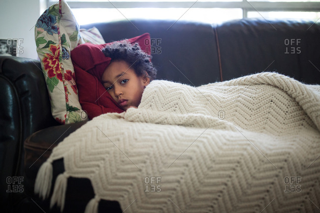 Little girl resting on couch under a blanket