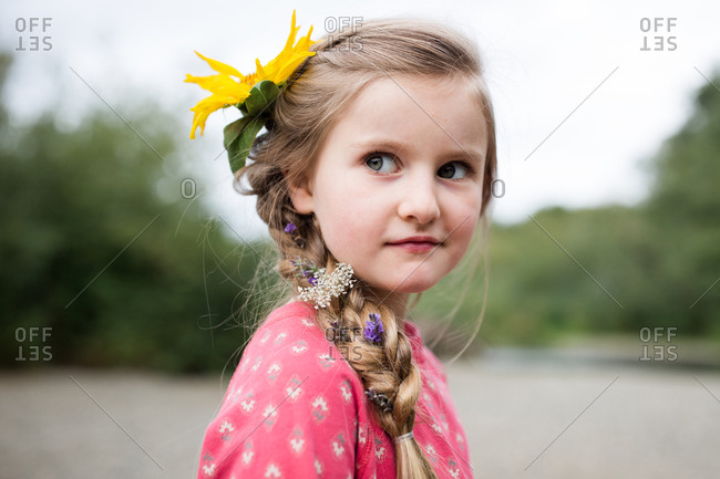 Portrait of a young blonde girl with a yellow flower in her hair