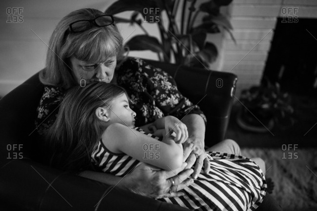 Grandmother cuddling with little girl in chair