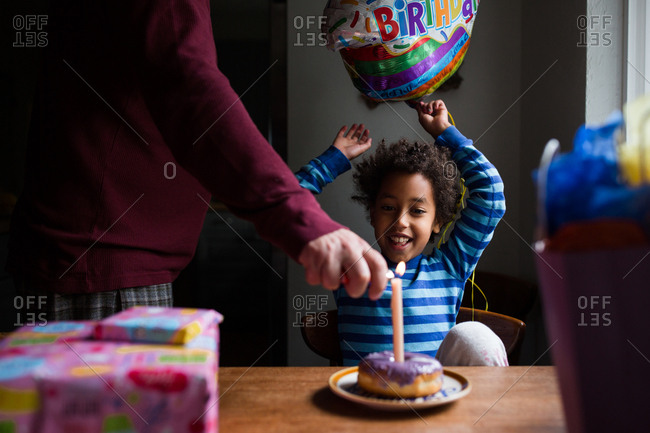 Father lighting little girl's birthday candle