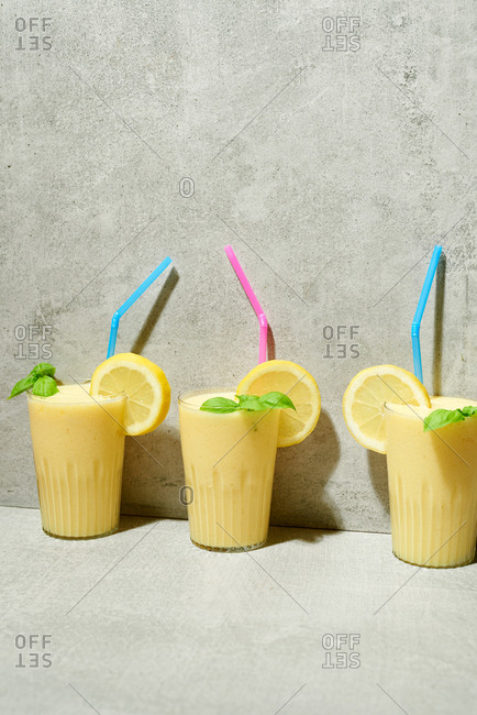 Mango and pineapple smoothies on concrete background