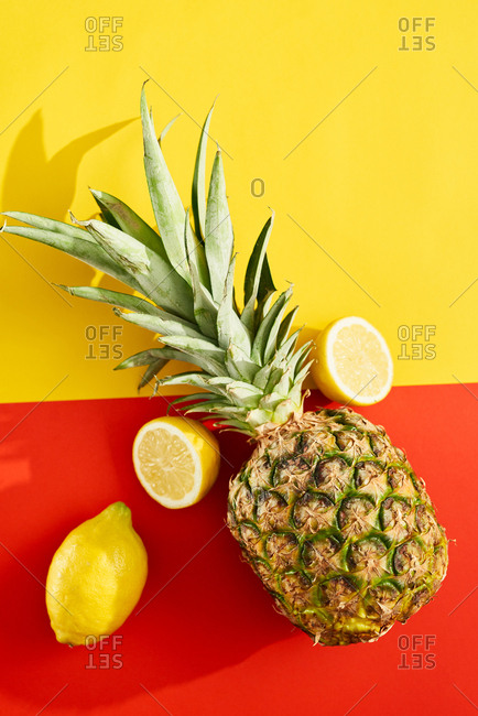 Pineapple and lemons on red and yellow background
