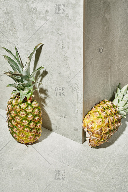 Two halves of a pineapple on concrete background