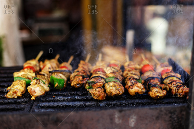 Row of chicken skewers with vegetables cooking on hot grill