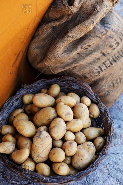 Overhead view of potatoes in basket next to sack of potatoes