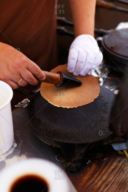 Ice cream vendor preparing flat waffle before rolling into cone shape