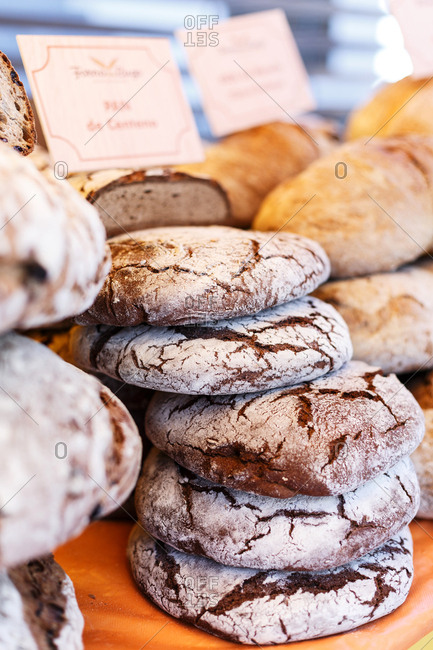 Stacks of freshly baked bread loaves at market stall