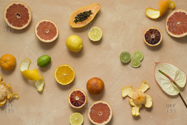 Various citrus fruits and papaya on a pink background