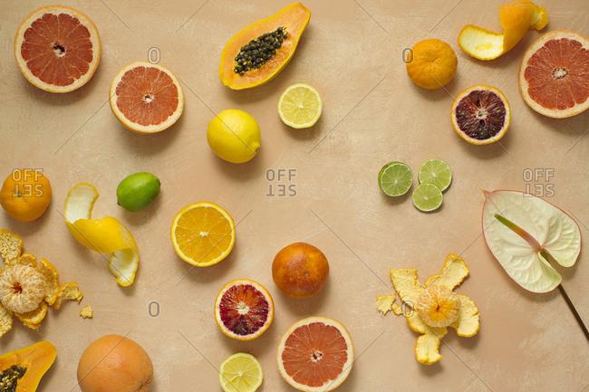 Citrus fruits and papaya on a pink background