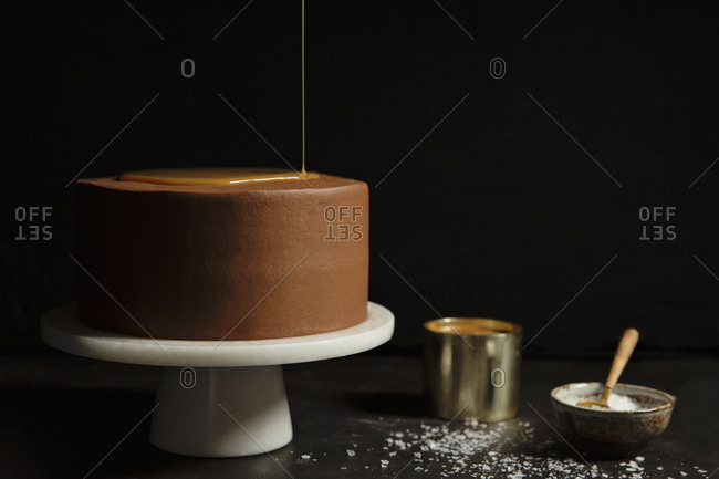 Chocolate cake being drizzled with caramel