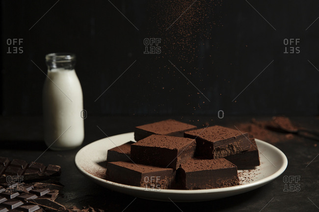 Brownies being sprinkled with cocoa powder served with milk
