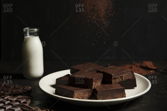 Brownies being sprinkled with cocoa powder